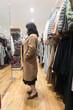 オーバーコートを試着する女性