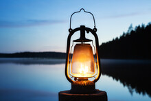 Vintage Kerosene Lantern Near A Lake At Night. Misty Calm Lake And Forest On Background.