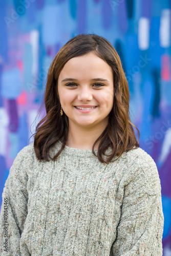 Fotografie, Obraz Young girl wearing a sweater in the winter standing outside near a bright colored wall with blue, pink, and purple