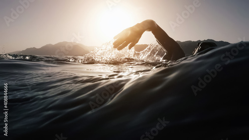 Obraz Athletic young man swimming at sea. Professional triathlon swimmer in ocean water. Young man athlete practicing at open water - fototapety do salonu