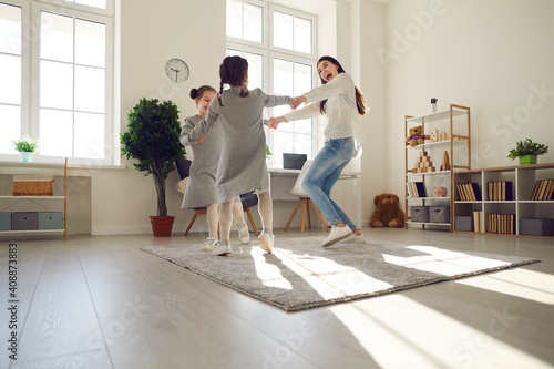 Happy family having fun at home. Overjoyed young woman and children playing together. Cheerful mother and daughters dancing and laughing on warm floor rug in cozy sunny living-room of their own flat