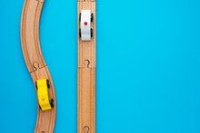 Baby Kid Toys Background. Toy Train And Wooden Rails On Blue Background. Top View