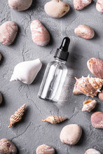 Skin Care Essence Oil Dropper In Glass Bottle Near To Seashells And Pebbles