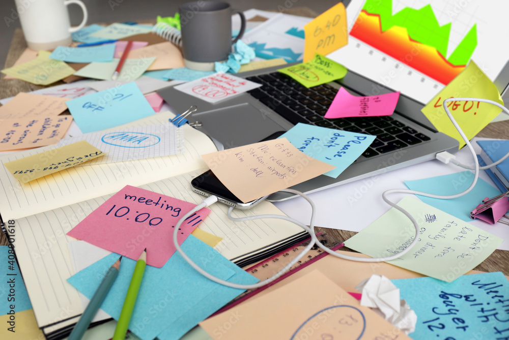 Fototapeta Laptop, notes and office stationery in mess on desk. Overwhelmed with work