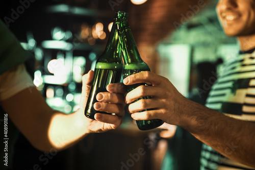 Fototapeta Men with beer celebrating St Patrick's day in pub, closeup