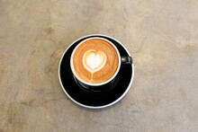 Cup Of Hot Cappucino On Concrete Background.Heart Shape Art Latte Symbol Of Love