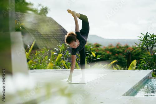 Fototapeta Woman yoga on the terrace. Home training. Holiday yoga