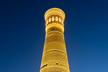 Vertical Photo Of Great Minaret Of The Kalon Illuminated During The Blue Hour. Kalyan Minaret Is Located In Poi Kalan Complex In Bukhara, Uzbekistan.