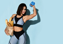 Young Fitness Brunette Woman In Modern Sportswear Top And Shirts Stands Holding Craft Shopping Bag Full Of Bread And A Dumbbell In The Other Hand Over Blue Background. Diet And Slimming Concept