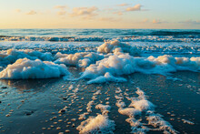 Beautiful Sea, Sandy Beach, Seafoam, And Clear Blue Sky On Sunset. Wild Beach Of The Sea Of Okhotsk, Sakhalin Island, Russia. Natural Landscape Background With Copy Space.