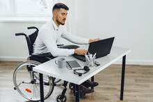 Positive Disabled Young Man In Wheelchair Working In Office