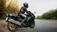 Motorcyclist Rides Along A Forest Road. Have Fun On An Empty Road On A Sports Motorcycle. Copy Space For Your Customized Text