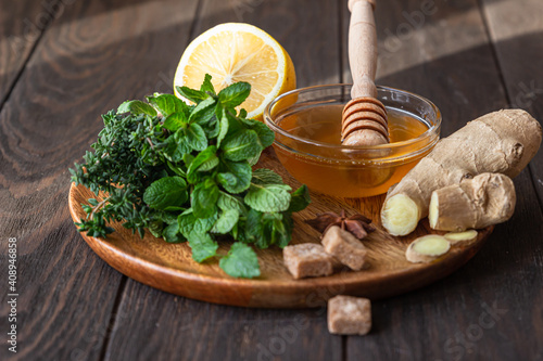 Photo Mint, thyme, ginger root, lemon, honey and brown sugar on wooden plate