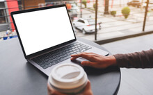 Mockup Image Of A Woman Using And Touching On Laptop Computer Touchpad With Blank White Desktop Screen While Drinking Coffee
