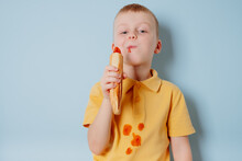 A Child Eating A French Hot Dog And Stains His Clothes With A Ketchup Stain. Place For Text