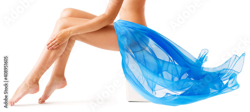 Obraz Beauty Woman Legs Skin. Leg Wax Depilation. Body Care. Flying Blue Fabric Wave. Isolated White - fototapety do salonu