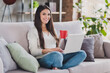 Photo of pretty cheerful girl hold laptop mug sit couch drink wear white pullover in living room home indoors
