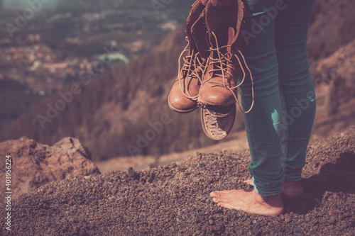 Foto Barefoot woman travel with broken shoes - concept of freedom and alternative fre