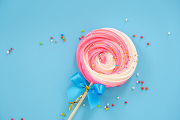 Pink and white Lollipop Meringue Dessert Sprinkled with Cocoa Powder Skewers are adorned with a blue bow on a blue background with colorful toppings.