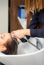 A Female Hairdresser Is Rinsing The Hair Of A Young Woman In A Sink After Shampooing In A Hair Salon