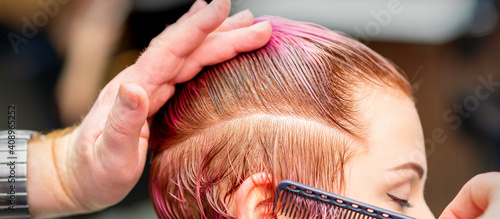 Foto Male hairdresser combing hair making short pink hairstyle for a young caucasian