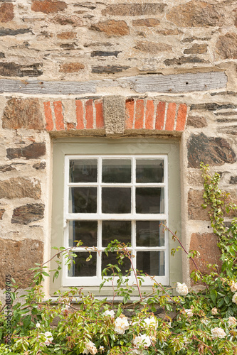 Old square wooden window in an old stone cottage wall with garden plants underneath