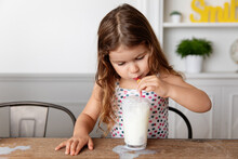 Cute Little Girl Blowing Bubbles With Straw In Glass Of Milk