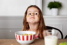 Goofy Little Girl With Cereal Stuck On Face At Kitchen Table