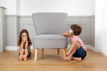 Siblings Playing With Tin Can Telephone In Living Room