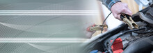 Hands Of Car Mechanic Using Car Battery Jumper Cable; Panoramic Banner