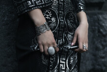 Hands With Bracelets And Rings And A Black Dress