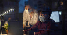 Colleagues In Safety Mask Discussing Statistics Looking At Laptop Screen Working Late In Office