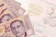 2 Singaporean dollars bills lies in stack on background of big semi-transparent banknote. Abstract business background