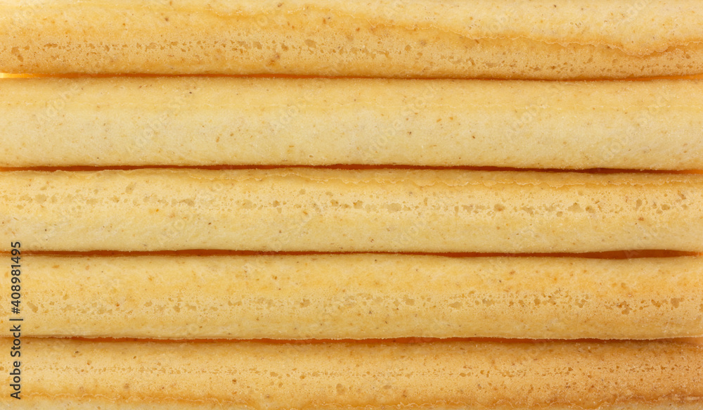 Fototapeta Close view of small dried breadsticks in rows.