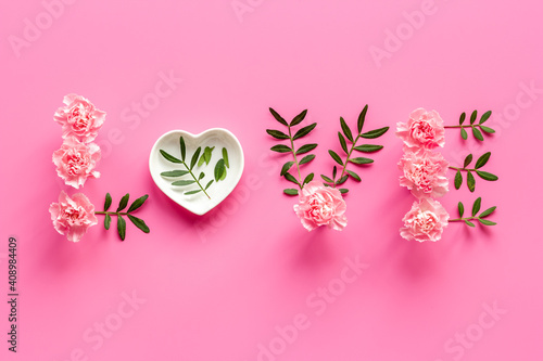 Word Love made of pink flowers and green leaves, overhead view