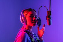 Young Singer In Wireless Headphones Singing Song In Microphone On Purple