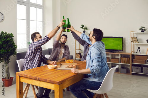 Obraz Cheers! Friends sitting at table at home and clinking beer bottles. Group of happy young men eating pizza, enjoying drinks, watching football match on TV, having fun and enjoying good time together - fototapety do salonu