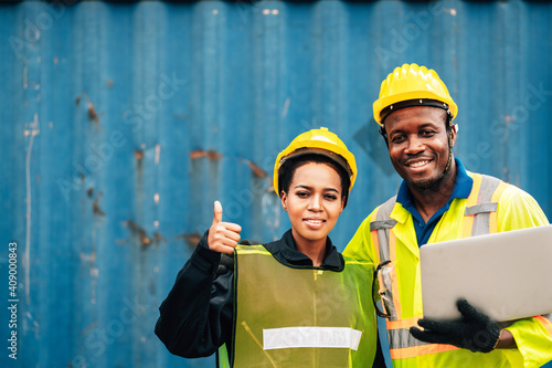 Fotografiet workers team man and woman smilling in safety jumpsuit with yellow hardhat and use laptop check container at cargo warehouse