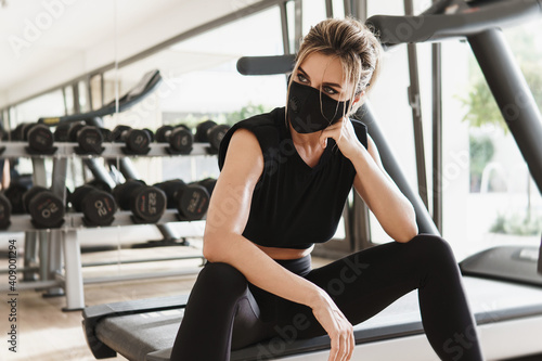 Fototapeta Young athletic woman wearing a prevention face mask during her fitness workout. obraz