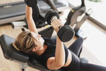 Young Athletic Woman Doing Bench Press Using Dumbbells