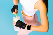 Cropped Photo Of Fitness Girl With Protein Shake Whey. Bodybuilding Concept On Blue Background.