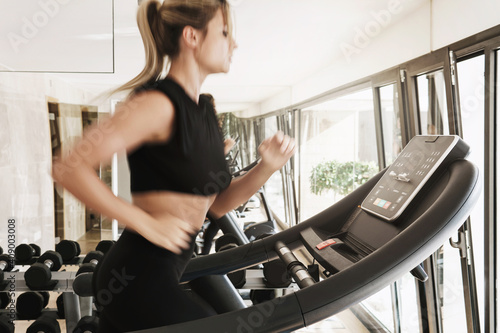 Obraz Athletic woman running on treadmill during fitness workout - fototapety do salonu