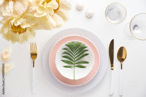 Effortless golden birthday dinner table decor. Pale yellow peony flowers. White dinner table, white and gold utensils, decorated with season flowers and palm leaves. © tilialucida
