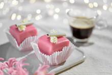 Valentine Petit Fours With Marzipan Icing And Cream Flowers. Espresso Coffee In Glass Cup. Happy Valentine's Day Garland Of Lights On Ivory, Off White Textile Tablecloth. Pink Hyacinth Flower.