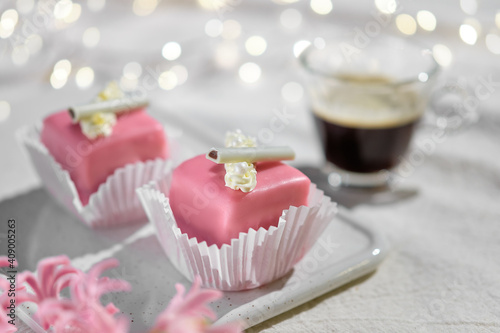 Valentine petit fours with marzipan icing and cream flowers. Espresso coffee in glass cup. Happy Valentine's day Garland of lights on ivory, off white textile tablecloth. Pink hyacinth flower. © tilialucida