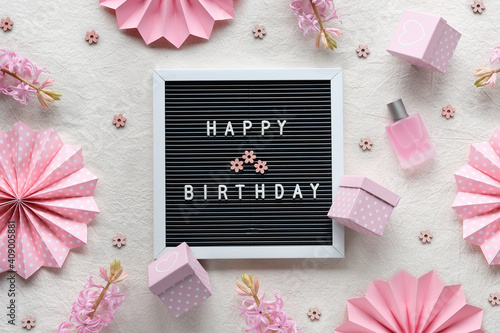 Text Happy Birthday on letter board, letterboard. Creative flat lay, top view on cream white textile. Party decor, paper fans, gift boxes. Natural pink hyacinth flowers, glass bottle with perfume. © tilialucida