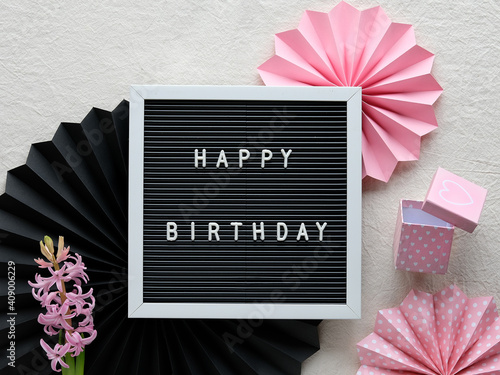Text Happy Birthday on letter board, letterboard. Creative flat lay in pink and black on cream white textile. Party decor, paper fans, sugar hearts and pink gift box. © tilialucida