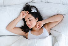 Beautiful Caucasian Girl Waking Up In Cosy Bed With White Linen In The Morning