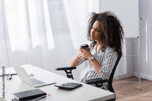 Obraz displeased african american freelancer holding paper cup near laptop on desk - fototapety do salonu