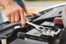 The Hands Of A Skilled Mechanic Are Holding A Wrench To Tighten A New Car Battery Replacement Nut, Car Care Concept And To Check Battery Health. And Engine